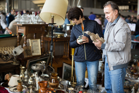 Loving mature couple choosing vintage goods at flea market