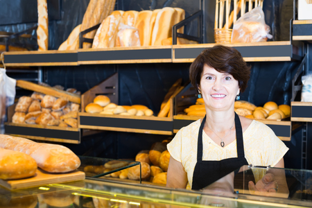 Portrait of attentive female baker with fresh bread smiling in bakery