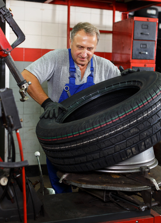 Mature man car mechanician removing tire from wheel disc in auto repair shop