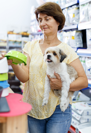 Nice woman visiting pet shop in search of dog bowl for feeding her cute havanese Фото со стока