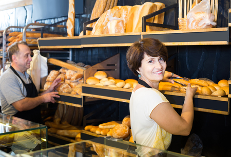 adult  staff offering fresh baguettes and buns in bakery