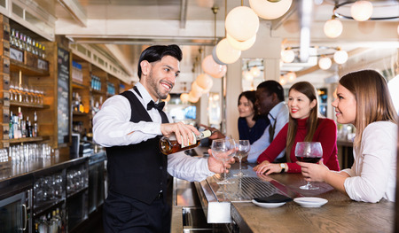Happy  smiling barman is servicing young people who are relaxing in bar indoor. 版權商用圖片