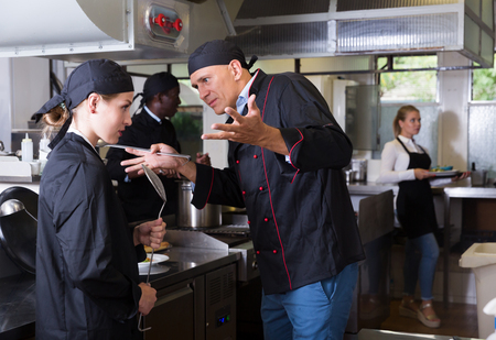 Exasperated head chef scolding upset female employee in kitchen of restaurant