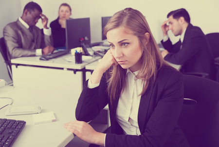 Tired businesswoman standing in office on backround  with working colleagues Imagens
