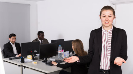 Elegant young businesswoman politely welcoming to modern open plan office
