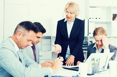 Outraged female manager expressing dissatisfaction with teamwork of colleagues at meeting