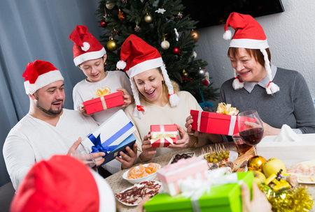 Big friendly family celebrating Christmas with gifts against backdrop of decorated fir tree