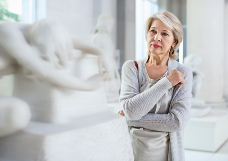 Adult cheerful positive  female looking at artwork sculpture in the museum indoors