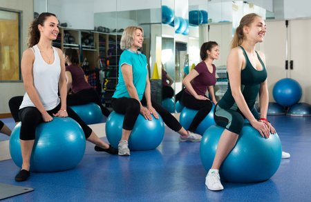Different age people jumping on exercise ball during group train