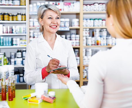 Cheerful  smiling mature female seller suggesting care products to young customer in specialized shop Stock Photo
