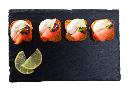 Top view of canapes on toasted bread with smoked salmon, olives and creamy sauce on black serving board. Isolated over white background
