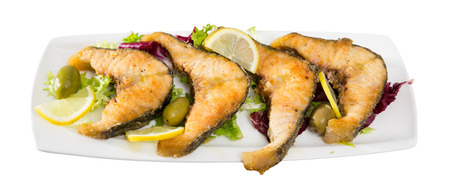 Tasty fish dish – roasted sturgeon fish served with lemon and olives. Isolated over white background