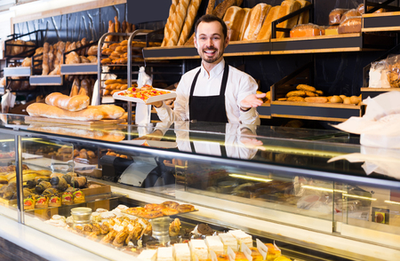 smiling spanish  male shop assistant demonstrating fresh delicious pastry in bakery