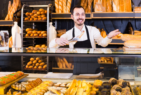 smiling american  male shop assistant demonstrating fresh delicious pastry in bakery
