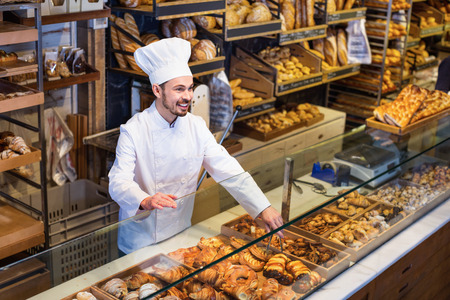 Smiling happy cheerful positive man baker showing warm tasty croissant in bakery