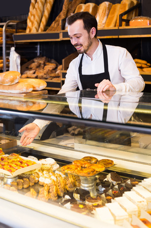 smiling italian male shop assistant demonstrating fresh delicious pastry in bakery
