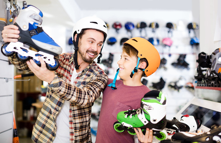 Young american father and son deciding on new roller-skates in sports store