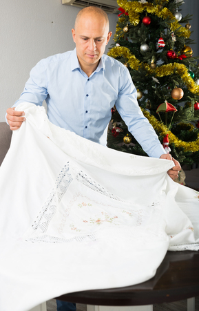 Portrait of young man preparing table for New Year dinner, spreading tablecloth Stock Photo