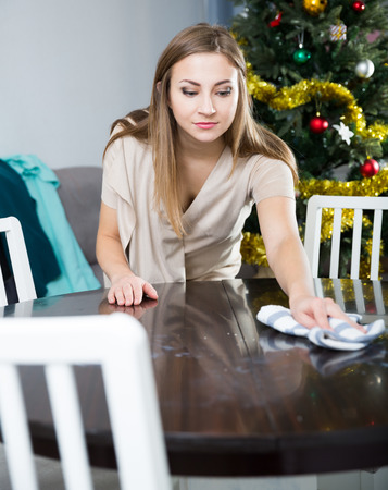 Happy girl preparing for celebration of New Year at home, wiping surface of table