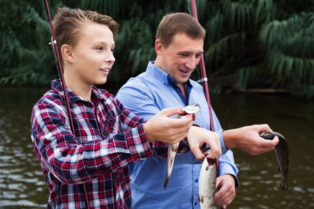 Smiling teenage boy and his father holding taken freshwater fish in  hands