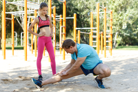 Happy family of father and preteen girl stretching together after training outdoors