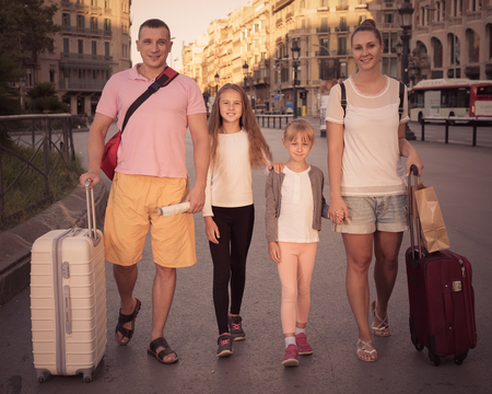 Happy ukrainian traveling family of four strolling with luggage along European city street