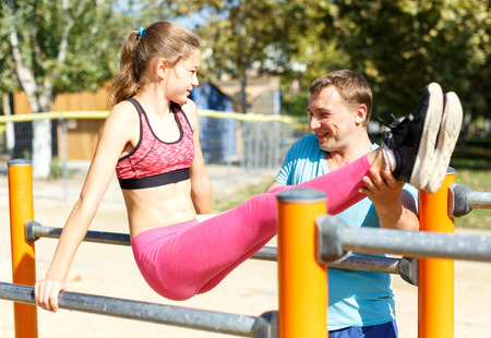 Father helping his sporty tweenager daughter do l-sit on parallel bars during workout on summer sports ground