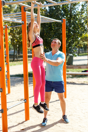Smiling athletic man and tweenager girl exercising together on horizontal bar on summer sports ground