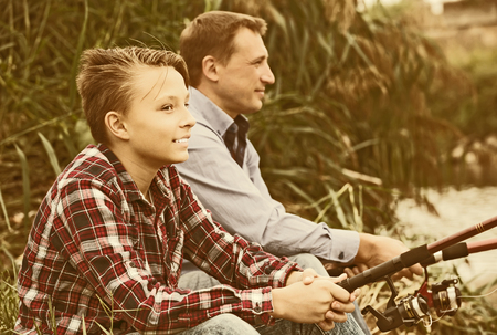 Positive father and boy fishing together on freshwater lake from shore 写真素材