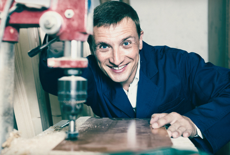 Smiling diligent man wearing protective workwear operating automatic screwdriver in wood workshop Banque d'images