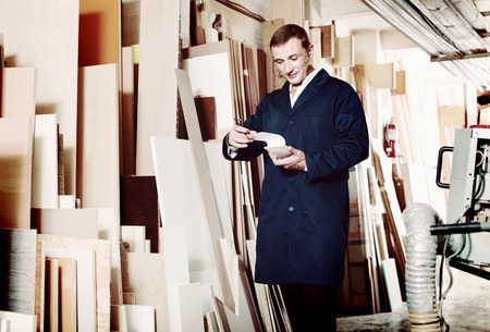 Smiling glad man wearing protective workwear standing with plywood in store