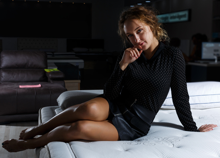 beauty woman in black clothes posing on bed with new mattress in furnishing salon