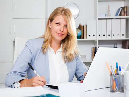 Portrait of positive lady business adviser working at office with laptop on table