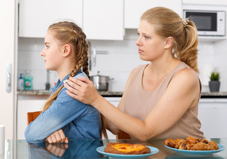 Mother apologizing to her teenage daughter after quarrel in kitchen interior