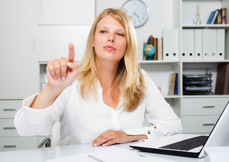 Positive business lady sitting at workplace with laptop and pointing to invisible screen