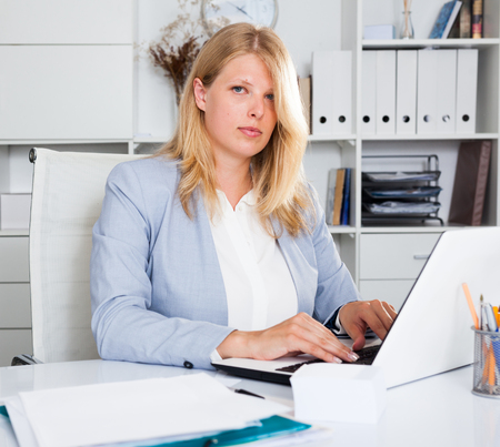 Portrait of smiling business woman working at her workplace with laptop on table