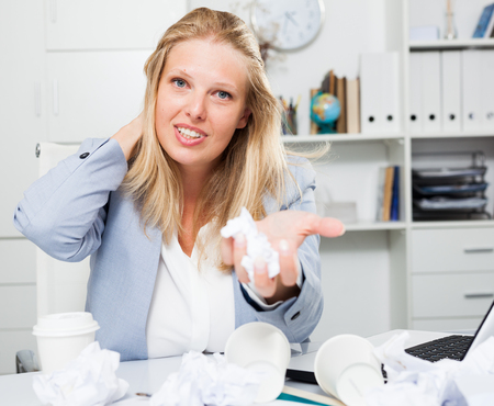 Frustrated tired businesswoman sitting at workplace among crumpled papers