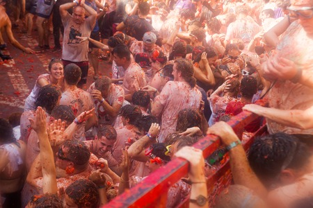 BUNOL, SPAIN - AUGUST 30, 2018: Battle of tomatoes - tomatoes madness.  La Tomatina festival in spanish town where people throw tomatoes