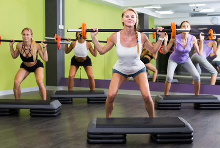 Smiling athletic girls during workout in gym with barbell Stock Photo