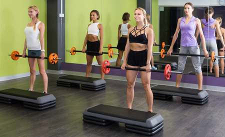 Group of women performing weight lifting workout at gym