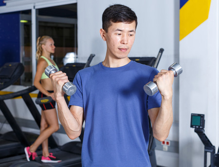 Young man doing exercises with dumbbells during fit training at gym Stock Photo