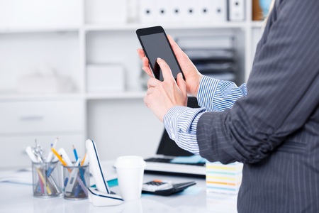 Woman using touchscreen phone on background with blured office interior