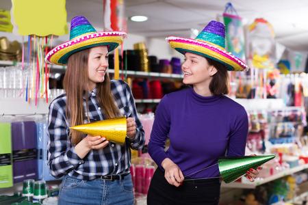 Portrait of active comically dressed girls joking in festive accessories shop Reklamní fotografie