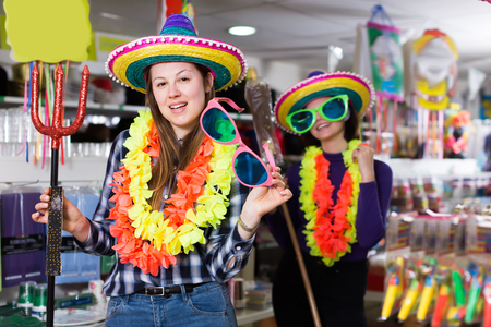 Portrait of happy active comically dressed girls joking in festive accessories shop