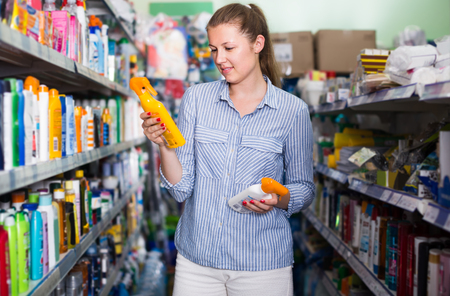 smiling woman choosing bottles of sun protection from assortment indoors Stock Photo