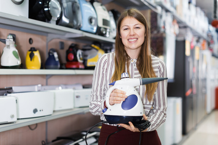 Young saleswoman offering steam cleaner in household appliances shop Imagens