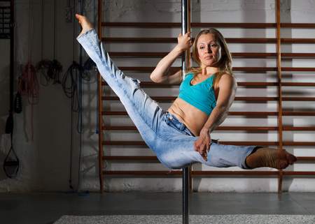 Attractive sports girl dancer engaged on pylon in semidarkness at gym Imagens