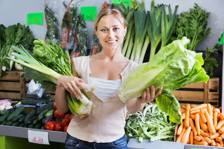 Portrait of positive glad  woman shopping fresh green celery, leek and lettuce in shop Stok Fotoğraf