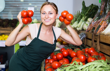 smiling young female seller wearing apron holding fresh ripe tomatoes on market