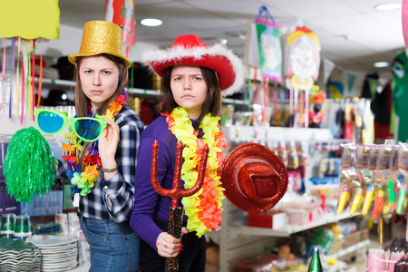 Young girl having fun in festival outfits store while preparing for party with her friend